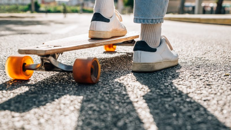 feet of a man on a skateboard in the street